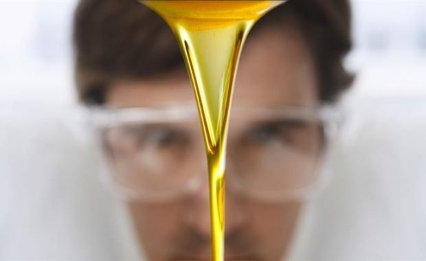 Man watching lubricating oil pour out of a container