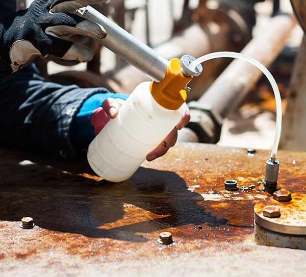 Lubrication technician taking oil sample with vacuum pump.
