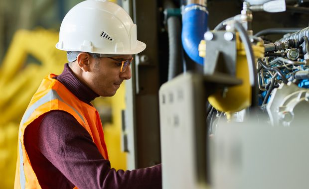 A man in a hard hat inspects a machine on a factory floor as part of a proactive maintenance program