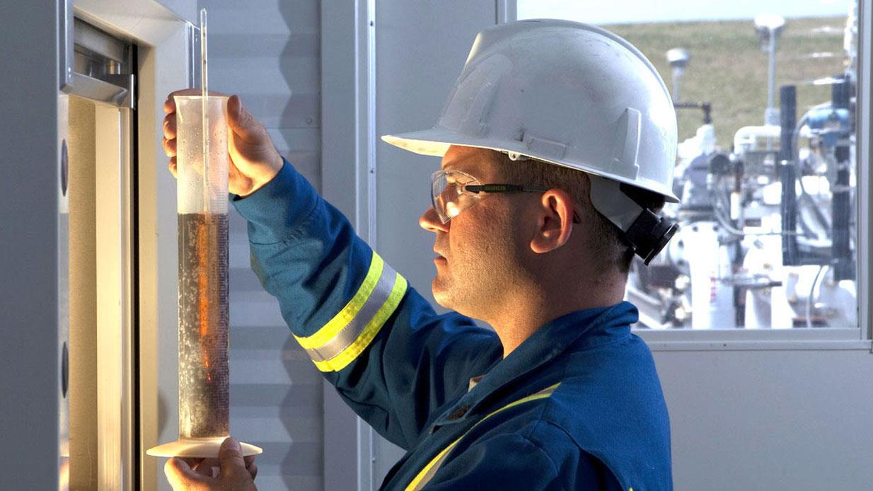 A maintenance or lubrication technician examines a sample of hydraulic fluid before it is analyzed.